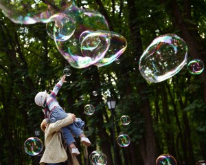 TOPSHOTS A girl plays on May 28, 2013 with soap bubbles during the Share Drive of Life charity event organized by the Kiev Chapter Ukraine motorcycling club for children with autism in a park in Kiev. The number of children with various forms of autism in Ukraine increased over the past five years by 2.35 times, and 2,791 children were under the supervision of child psychiatrists in 2012. AFP PHOTO /SERGEI SUPINSKY